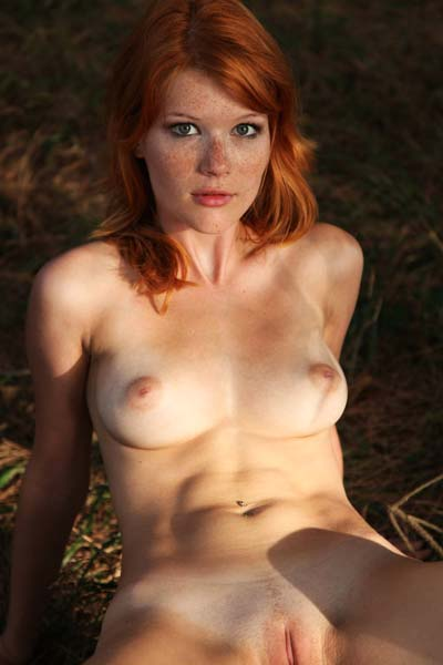 Redhead goddess Mia Sollis steps in the nude outdoors