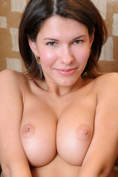 Suzanna A lovingly poses naked by the window displaying her alluring assets on the camera