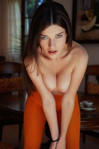 Sitting up on a table Serena Wood exposes her pink lustful twat