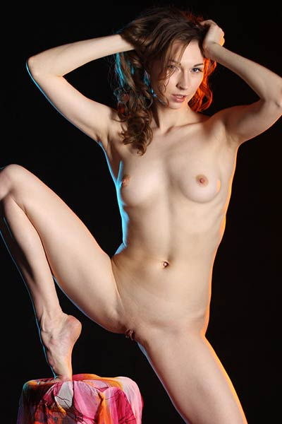 Tempting redhead sweetie presents her nubile body in the dark environment