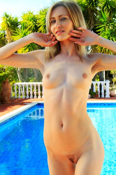 Delightful blonde babe strips naked by the pool baring her tasty pussy and peachy ass