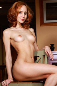 Redhead girl exposes her trimmed pussy and nice natural boobs