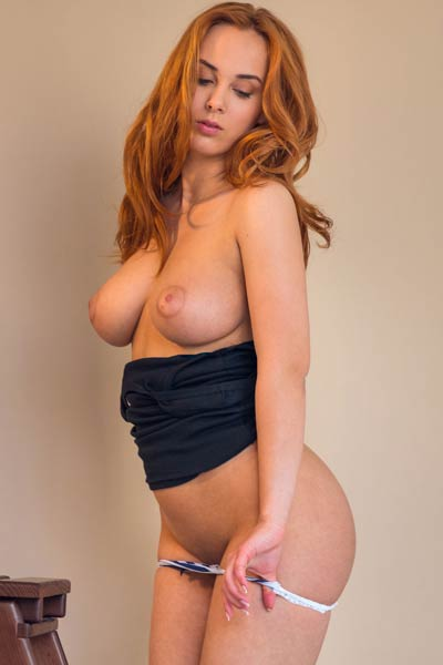 Redhead chick exposes her big juicy natural boobs and round booty on the chair