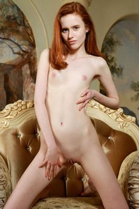 Tempting redhead girl stripping and posing naked on the armchair