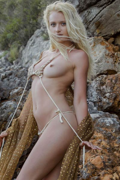 Tempting blonde doll gets nude on the rocks and teases with her sexiness