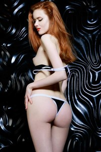 Redhead goddess poses naked in the dark presenting her perfect pale body