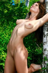 Perfectly sculpted brunette Yasmina showcasing her naked body outdoors in the woods