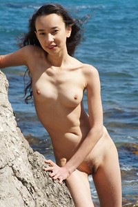 Erotic brunette poses naked on rock beach looking so good