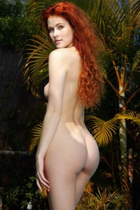 Fantastic redhead babe poses naked by the pool presenting her fabulous pale body