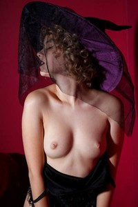 Delightful curly babe Chanel Fenn poses in the witch costume showing off her assets