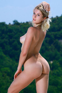Libby blonde with nice smile posing naked on her favorite mountain