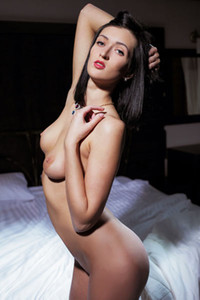 Dark haired bombshell presents her perfect curvy body as she poses on the bed
