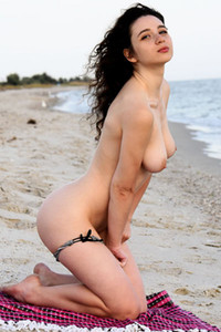 Adorable curly brunette eats melon on the beach exposing her sweet assets