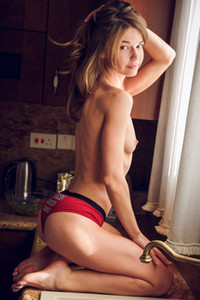 Pretty brunette model Nedda A reveals her small tits and tight ass in her kitchen