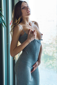 Delightful young beauty takes off her long dress and strokes her pale tits