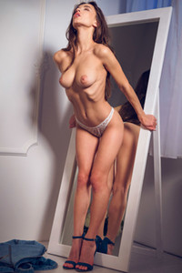 Foxy brunette bombshell strips and poses her smoking hot body by the mirror
